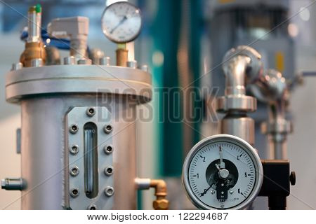 Image of industrial equipment with focus on mechanical pressure gauge.