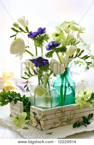 Ranunculus, anémona, fresia y eléboro en botellas de vidrio