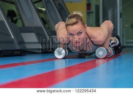 Beautifull blondy warming up and doing some push ups a the gym