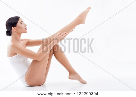 Portrait of body of attractive girl applying moisturizer on her legs. She is sitting and looking forward with pleasure. Isolated and copy space in right side
