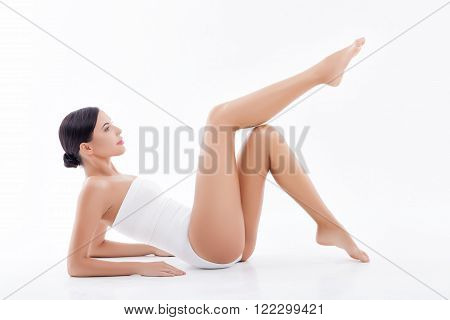 Beautiful girl is caring of her skin. She is lying and stretching her smooth leg up. The lady is looking at her foot with satisfaction. Isolated