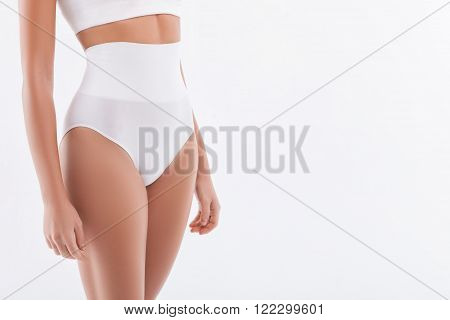 Close up of slim waist of young woman standing in hight stretching underwear. Isolated on white background and copy space in right side