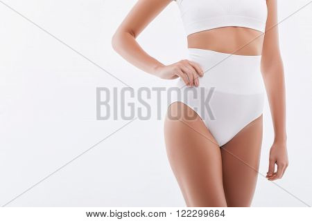 Look at my perfect figure. Close up of thin waist of young woman standing and posing. She is wearing stretching underwear. Isolated on white background and copy space in left side