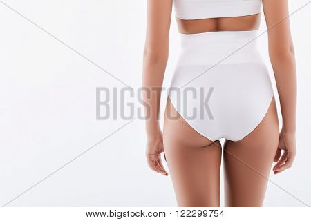 Close up of female buttocks. The young slim woman is standing in white underwear. Isolated on white background and copy space in left side