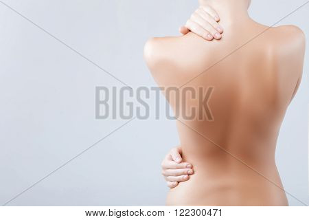 My skin is smooth and soft. Close up of female naked back. The girl is standing and touching her body carefully. Isolated and copy space in left side