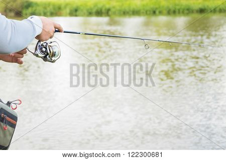 Young fisherman on the river bank. Fisherman caught a perch and holds it in his hands.