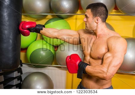 Man in boxing gloves, training in a hall fulfills kick. The strong man, a healthy lifestyle.