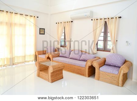 Complete set of rattan furniture with magenta pillows in white room