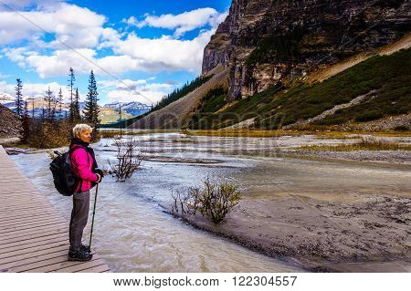 Senior Woman observing Glacial Water from Victoria and Lefroy Glaciers draining into Lake Louise in Banff National Park in the Canadian Rocky Mountains