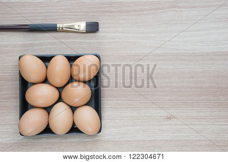 Eight Eggs in black square plate with a brush on wooden surface ready for Easter painting with space for text