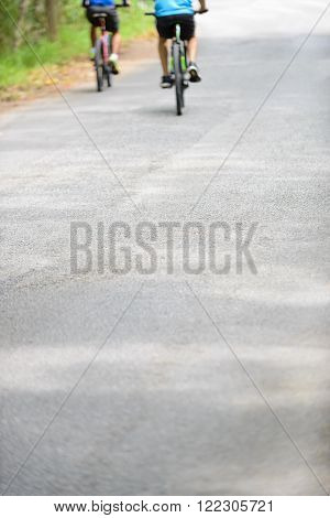 Rear view of 2 blurry biker cycling on the bicycle lane at a park. Space for text. Shallow depth of field