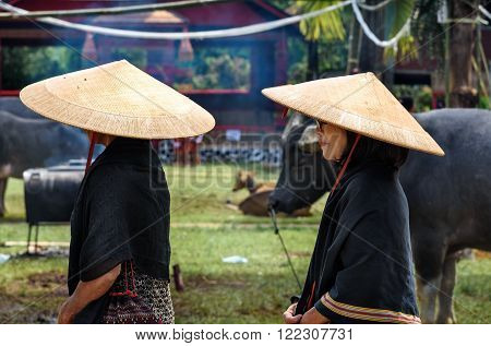 Group Of Women In Black And Conical Straw Hats  At Funeral Ceremony. Tana Toraja