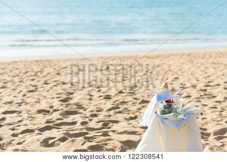 Chilled champagne and wine glasses in bucket setup on the beach.