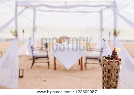 Blurry romantic dinner table setting on the beach at sunset. Focus on torch.