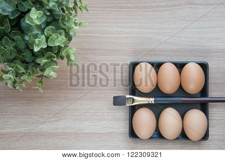 Selective focus of six Eggs in black square plate with a brush and small green plant on wooden surface ready for Easter painting with space for text