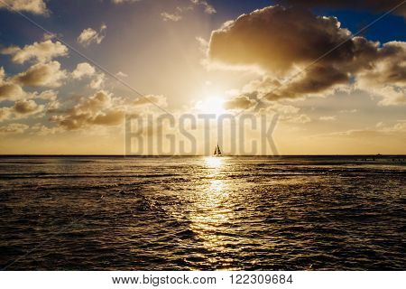 Silhouette of a boat sailing on horizon and of plane taking off at sunset with bright sun and twilight skies