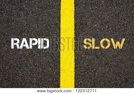 Antonym concept of RAPID versus SLOW written over tarmac, road marking yellow paint separating line between words