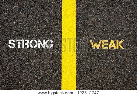 Antonym concept of STRONG versus WEAK written over tarmac, road marking yellow paint separating line between words