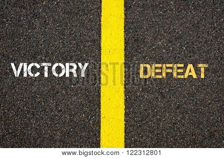 Antonym concept of VICTORY versus DEFEAT written over tarmac, road marking yellow paint separating line between words