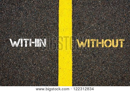 Antonym concept of WITHIN versus WITHOUT written over tarmac, road marking yellow paint separating line between words