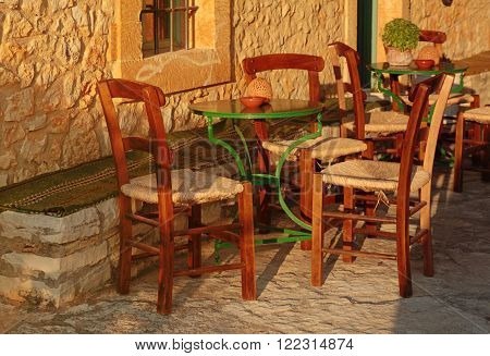 traditional greek outdoor restaurant on terrace empty table at an street village restaurant, Crete, Greece. Sunset light