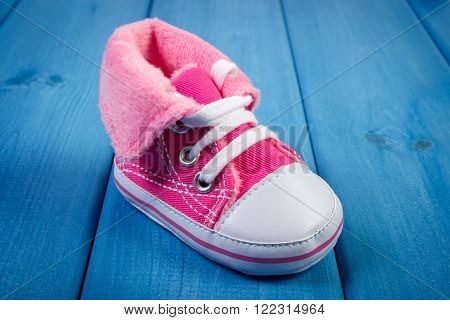 Pair of pink baby shoe on blue boards concept of extending family and expecting for baby