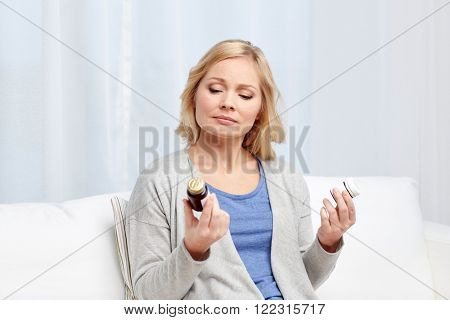 medicine, health care and people concept - woman looking at jars with medicine at home or hospital office