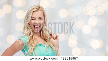 emotions, expressions, hairstyle and people concept - smiling young woman or teenage girl holding her strand of hair and winking over holidays lights background