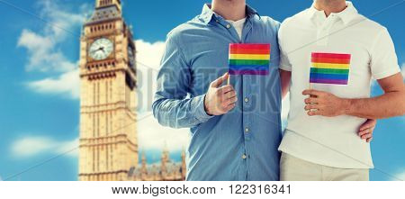 people, homosexuality, same-sex marriage, travel and love concept - close up of happy male gay couple holding rainbow flags and hugging from back over big ben tower in london background