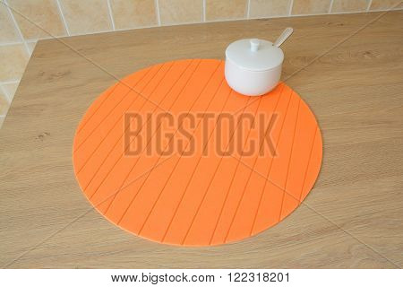 Round orange rubber tablemat and white sugar bowl with spoon on table