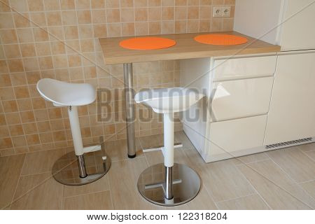 Two swivel stools and kitchen small table with orange rubber tablemats at wall covered with tiles