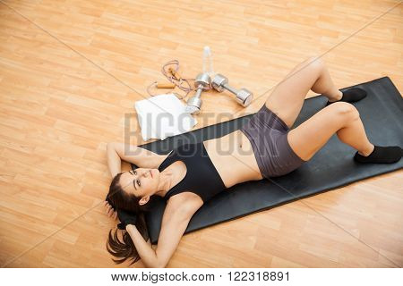 Portrait of a pretty Hispanic young woman taking a break between sets while doing crunches at the gym, as seen from above