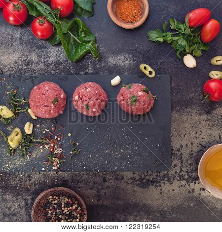 Minced meat mixture for meat balls and ingredients on dark background. Top view, vintage toned image, blank space