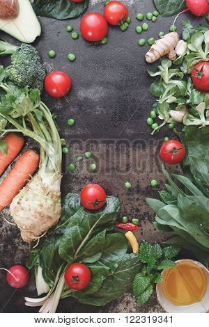 Fresh raw organic vegetable. Assortment of avocado, celery, carrots, wild garlic, desires, chard,spinach, broccoli, lamb's lettuce, tomatoes and peas. Top view, vintage toned image, blank space