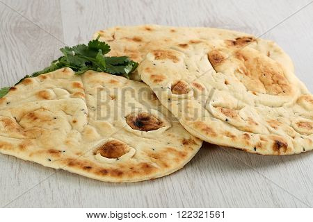 indian food two pieces of home made naan bread