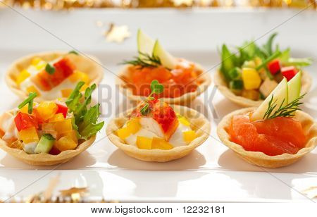 Christmas starter platter with appetizers.Tartlets with three different fillings(vegetable salad,crab salad and smoked salmon with apple)