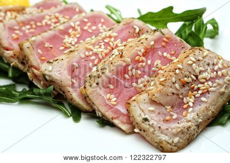 meat slices tuna with sesame seeds and herbs