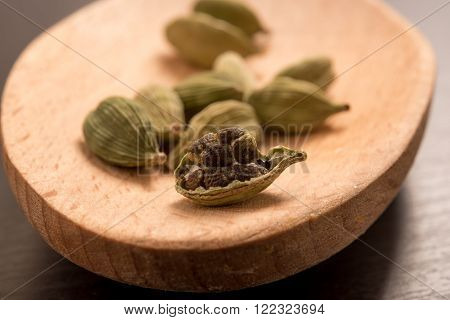 fresh dried cardamom cardamon seeds spice on a wooden spoon