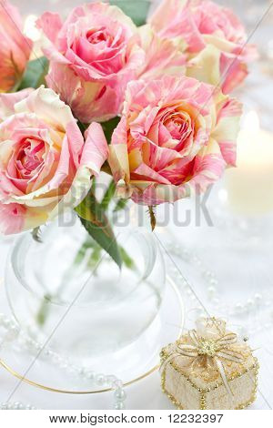 Strauß rosa Rosen in Vase, Kerze und kleines Geschenk-box