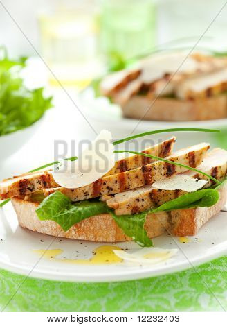 Open chicken Caesar sandwich on the white plate