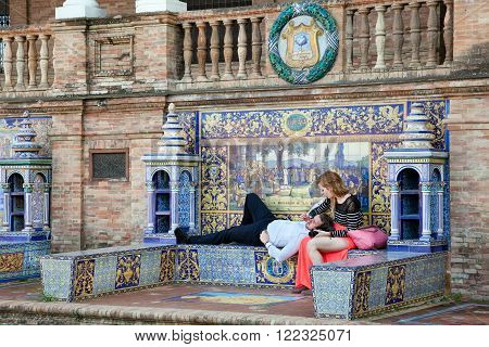 Sevilla, Spain - October 22, 2015: People in love are sitting at Ceramics Work At Plaza de Espana in Sevilla built in 1928 for the Ibero-American Exposition of 1929