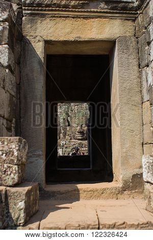 Stone head on towers of Bayon temple in window hole, Angkor Wat, Siem Reap, Cambodia