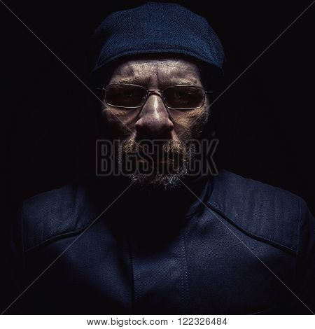 Portrait of a man in jacket wearing a glasses and beard. Reminds on soldier or police officer or similar.