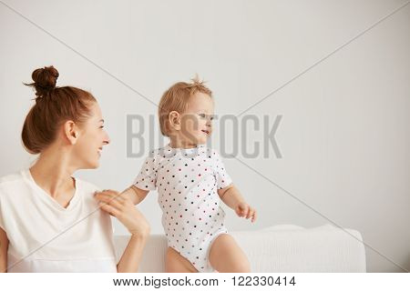 Young Mother With Her One Years Old Little Son Dressed In Pajamas Are Relaxing And Playing In The Be