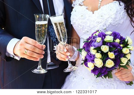 Bride and groom are holding champagne glasses and a bridal bouquet of white and purple flowers