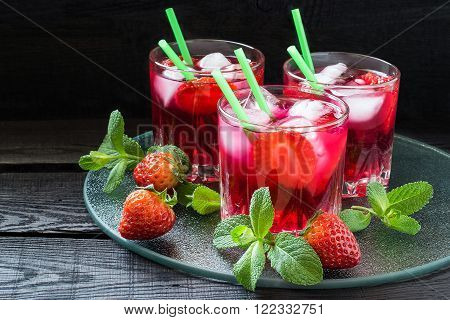 Three glasses of cold refreshing drink with strawberries ice and cocktail straws on a glass tray with fresh strawberries and mint
