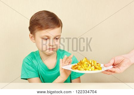 Little cute unhappy boy refuses to eat a french fries