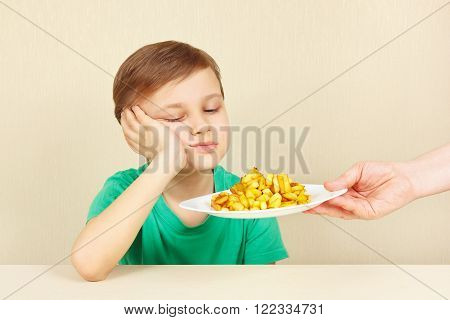Little cute unhappy boy refuses to eat a fries