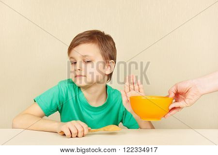 Little discontented boy refuses to eat a porridge