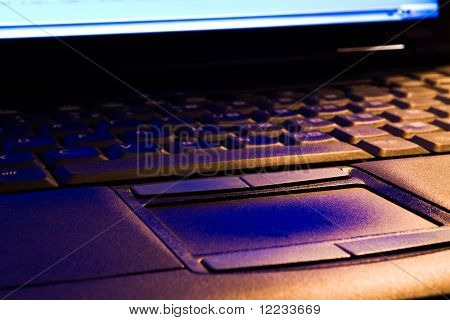 Laptop keyboard and touch-pad in blue and orange light